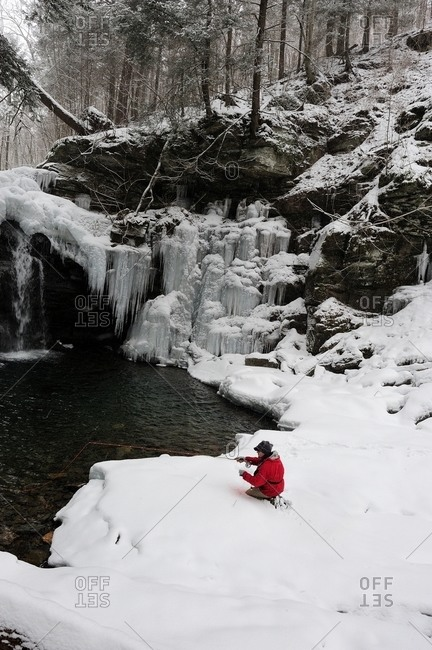 A man fly fishing on a snowy, cold winter day