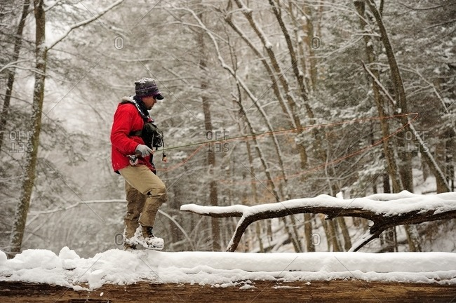 A man goes fly fishing on a cold, snowy winter day