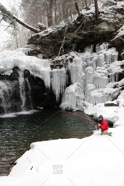 A man fly fishing on a cold, snowy winter day