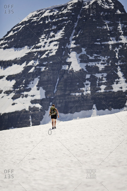 A female hiker in walks along the snowfield at Logan Pass, Montana on a hot summer day