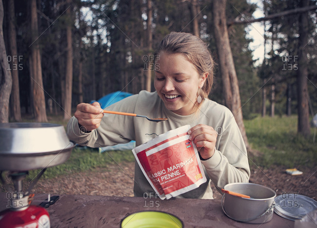 A young woman eats a backpacking meal while camping in the woods