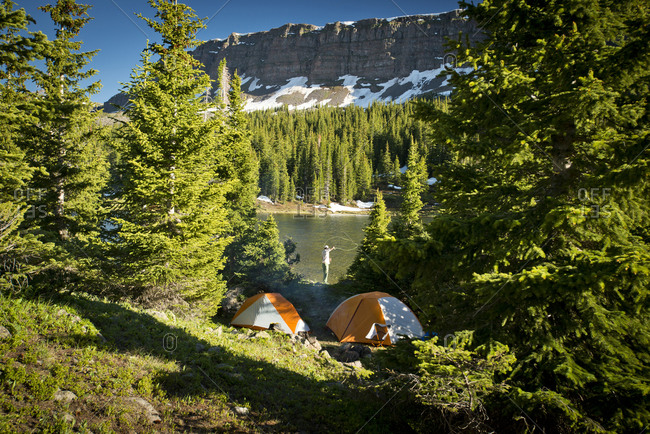 Two tents sit by a high alpine lake