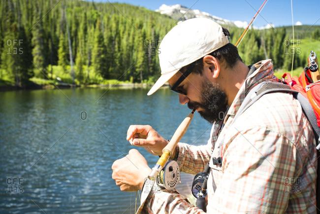 A fisherman prepares his rod next to a lake