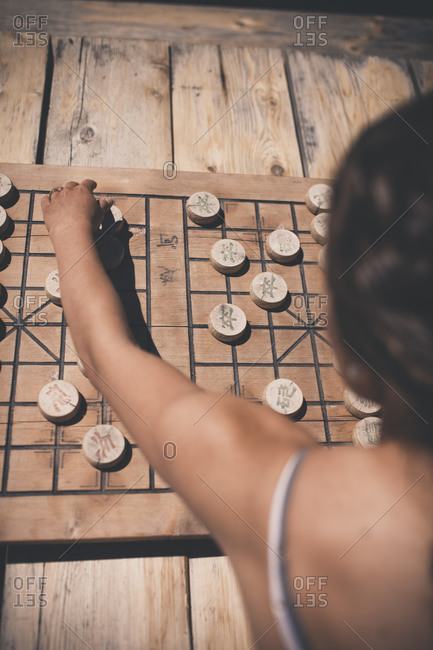 A young woman plays Chinese Chess
