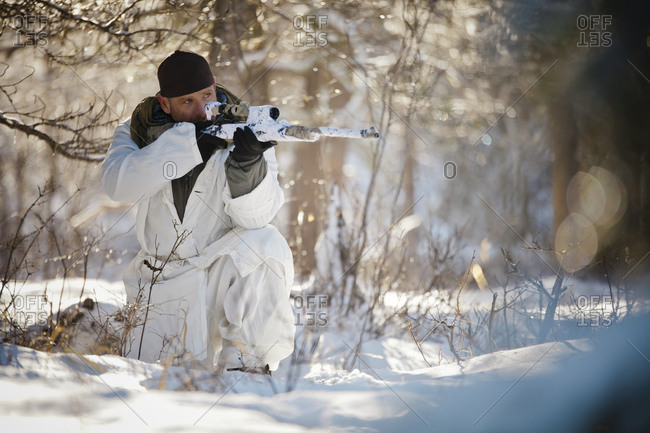 A hunter wearing a cold-weather camouflage outfit aims a rifle while crouching in a snow-covered forest