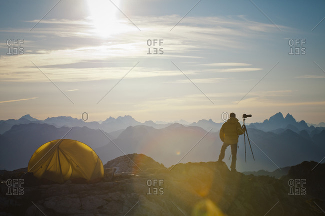 A photographer enjoys the view of the sunrise from his campsite on a rocky mountain ridge