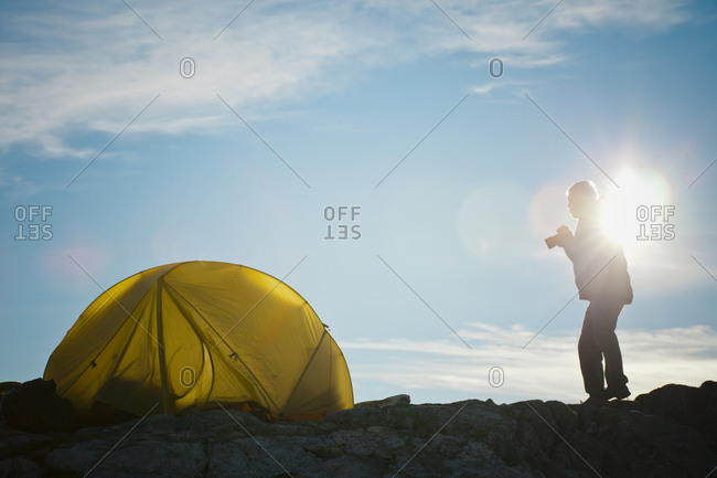 Silhouette of a photographer standing beside his tent shortly after sunrise