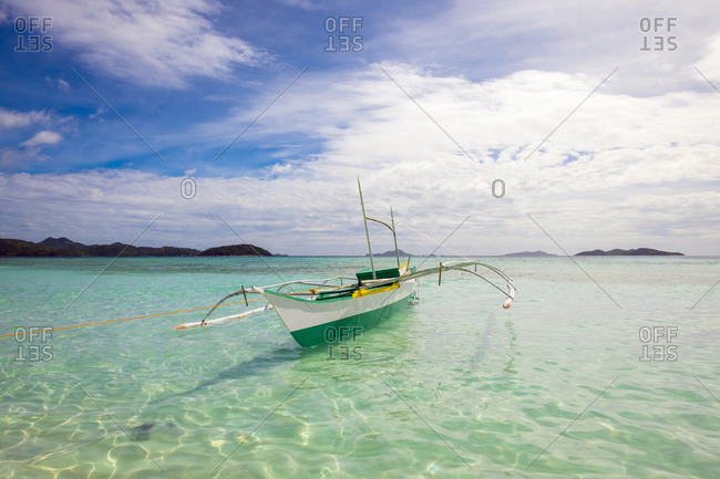 Small outrigger boat on the coast of Malcapuya Island, Philippines