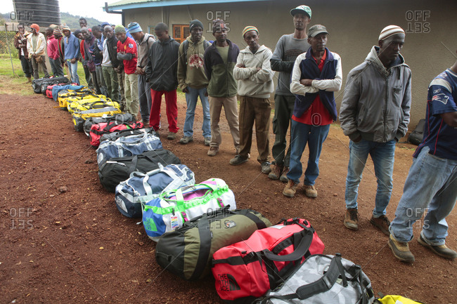 Kilimanjaro Region, Tanzania - August 24, 2013: Porters on Kilimanjaro are waiting in line next to expedition bags (duffels) of western trekkers, to get their load to carry
