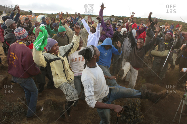 Kilimanjaro Region, Tanzania - August 24, 2013: Porters are happily singing and dancing in one of the camps on Kilimanjaro, to welcome their group of western hikers