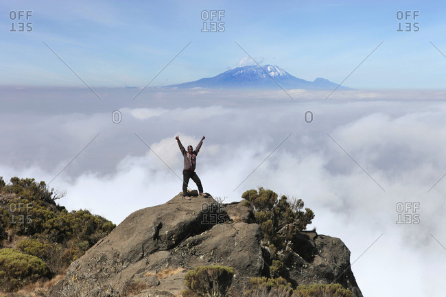 Mount Meru, Tanzania - August 21, 2013: A happy hiker with his hands in the air near the summit of Mount Meru, a trekking mountain in Africa In the background is Mount Kilimanjaro above a sea of clouds