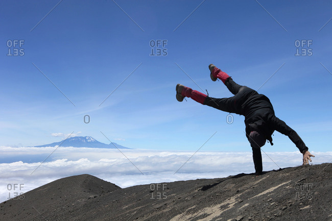 A male hiker is making a handstand in Mount Meru, Mount Kilimanjaro in the background