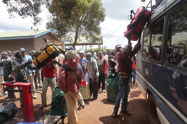 Kilimanjaro Region, Tanzania - August 22, 2013: Porters are lifting loads on a bus at the base of Kilimanjaro They are hired by western hikers to carry the bags up the mountain