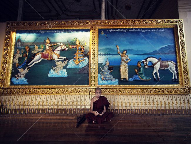 Mandalay, Myanmar - February 25, 2015: Young monk in the temple, sitting in front of the big picture, Mandalay