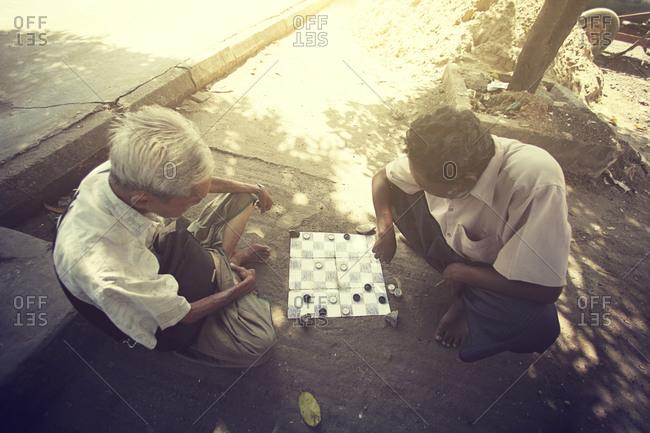 Yangon, Myanmar - February 26, 2015: Men playing checkers on the street