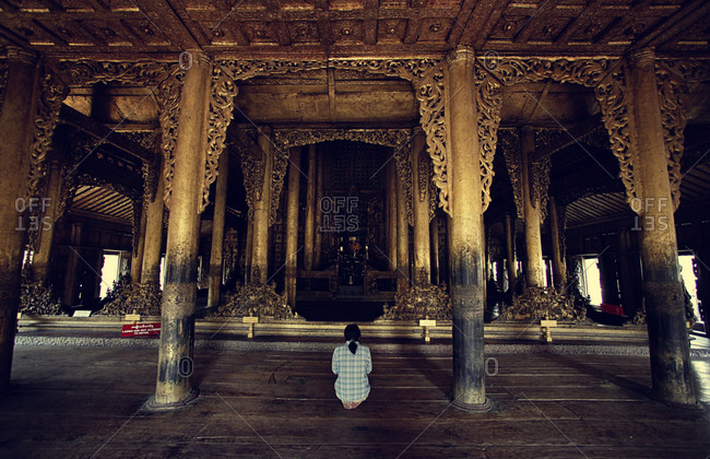 A woman praying in a temple in Myanmar
