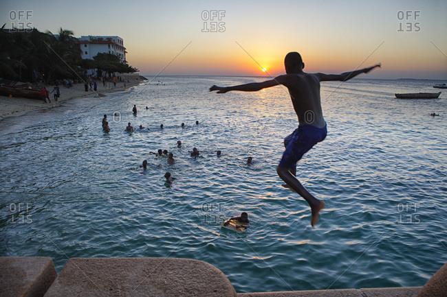 Zanzibar, Tanzania, East Africa - February 6, 2015: Boy jumps from boardwalk on Zanzibar