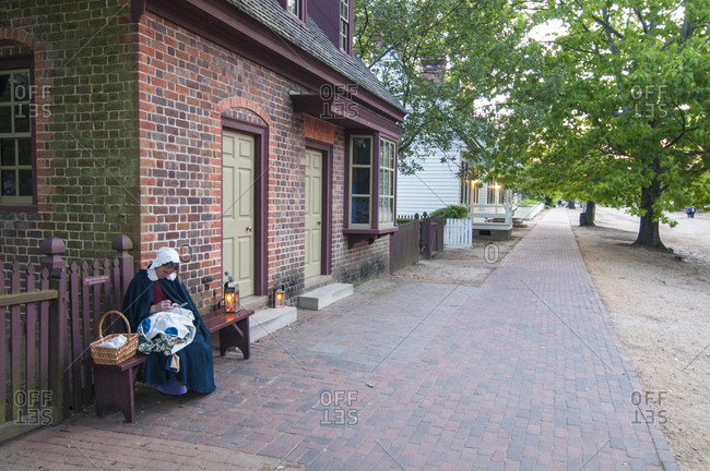 Colonial Williamsburg, Virginia, USA - April 19, 2010: Period actor sitting on a bench along a brick paved street in Colonial Williamsburg, Virginia