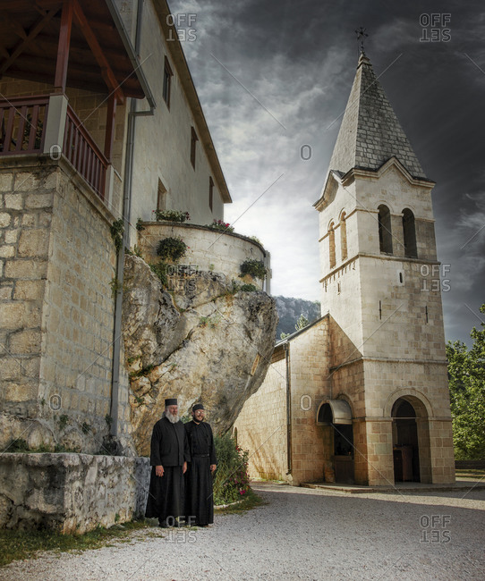 Ostrog, Montenegro - July 14, 2014: Two monks are under the terrace, next to the Church of the Holy Trinity, Ostrog, Montenegro
