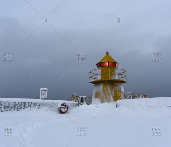 Short lighthouse in a snow storm in Reykjavik, Iceland
