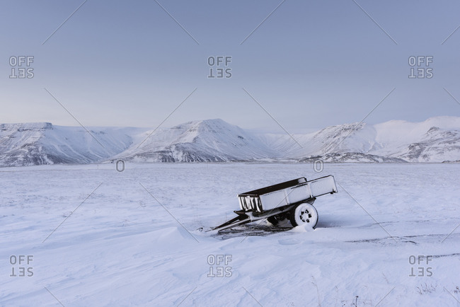 Abandoned utility trailer covered by snow