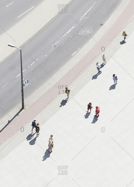 Elevated view of people walking on a sunny sidewalk