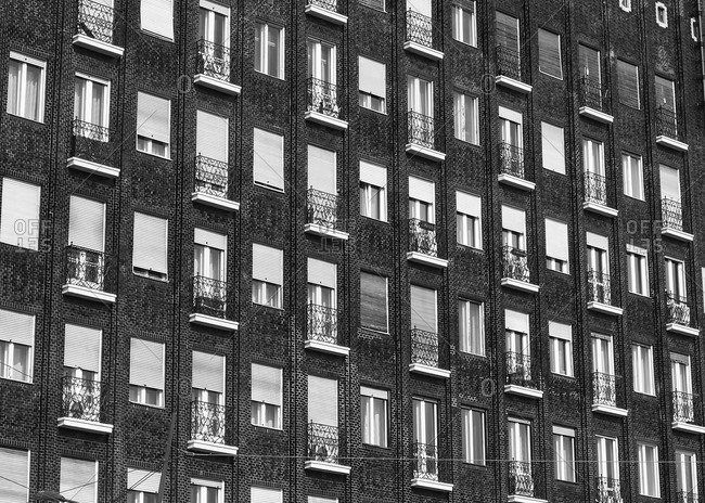 Rows of windows with small balconies on brick apartment building