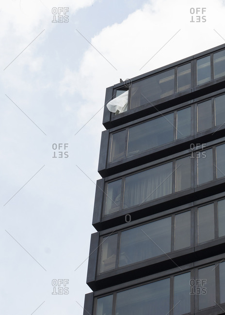 Curtain blowing out of window with bird above it on top floor of apartment building