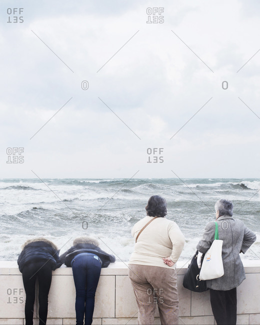 Two older women standing next to two young women bending over wall to view ocean