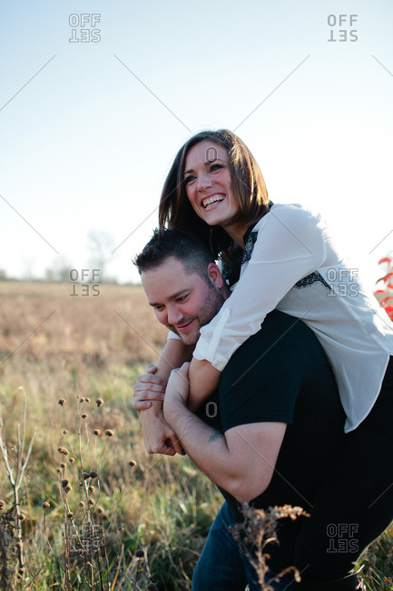 Man giving woman a piggyback ride in a grassy field