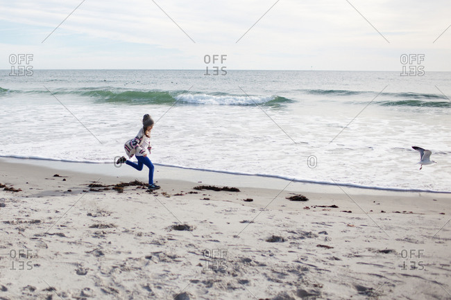 Young girl chasing a seagull on beach