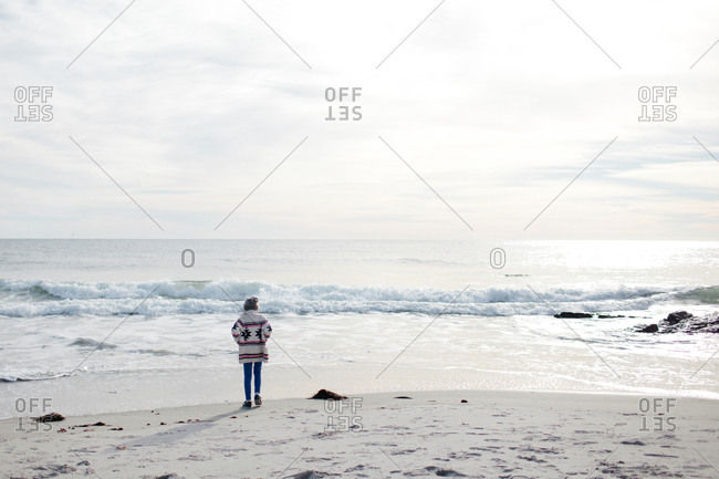 Back view of young girl in a sweater watching the waves on beach