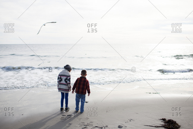 Brother and sister walking on beach in late afternoon in autumn