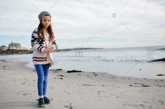 Girl in sweater and hat on beach on winter afternoon
