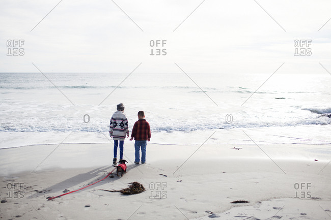 Two siblings and their pet dachshund on beach in winter