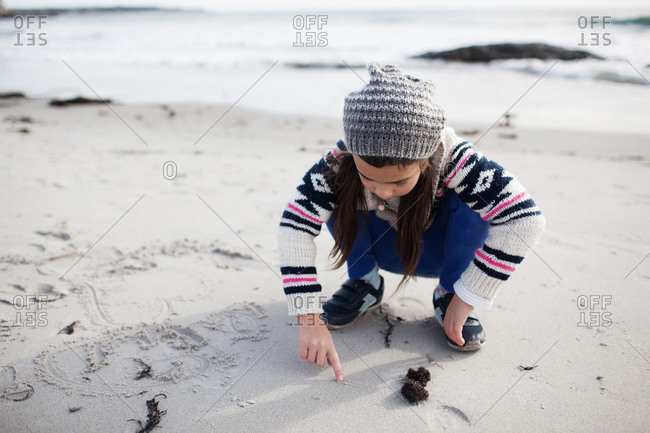 Young girl in hat and sweater drawing in sand on beach
