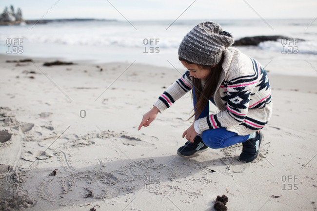Young girl making marks in sand with her finger