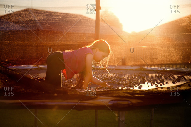 Girl playing with pebbles on a trampoline at sunset