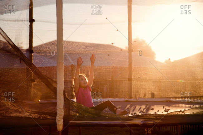 Girl playing with stones on a trampoline at sunset