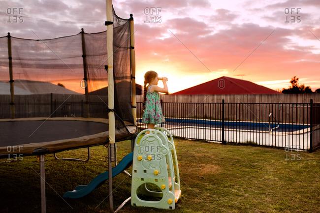 Girl playing with binoculars in her backyard at sunset