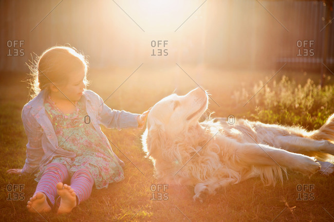 Girl petting her dog in backyard at sunset