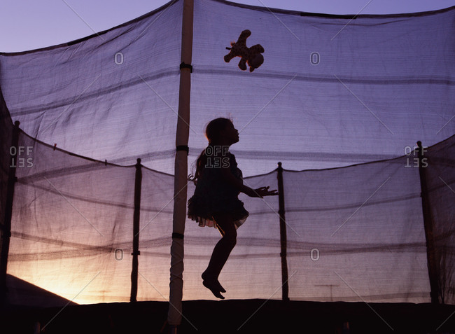 Girl playing on a trampoline at dusk