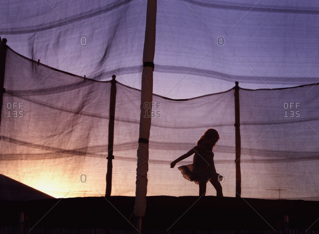 Girl jumping on a trampoline at dusk
