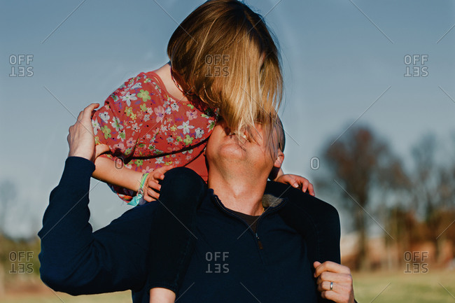 Girl riding on her father's shoulders
