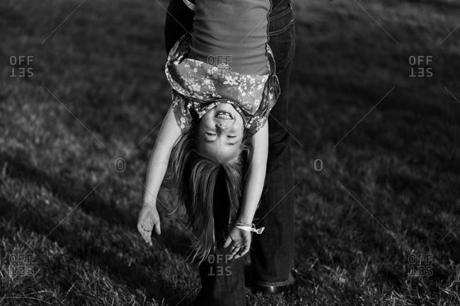 Parent dangling happy daughter upside down