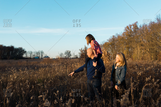Man points at tall grass while carrying daughter on his shoulders