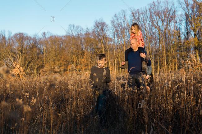 Family walking through tall grass at sunset