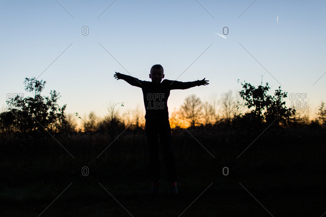 Boy silhouetted in field at sunset