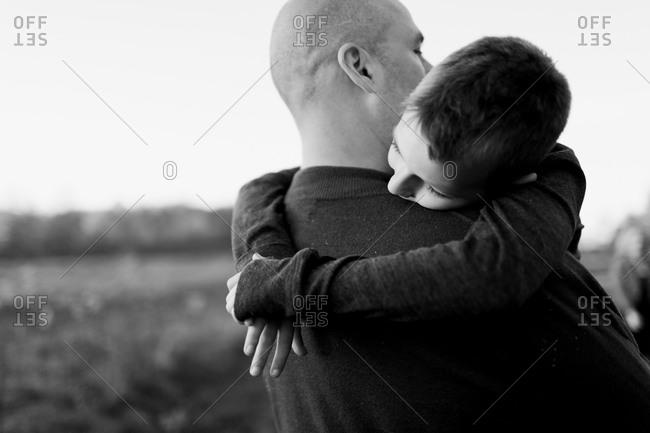 Boy hugs his father in field