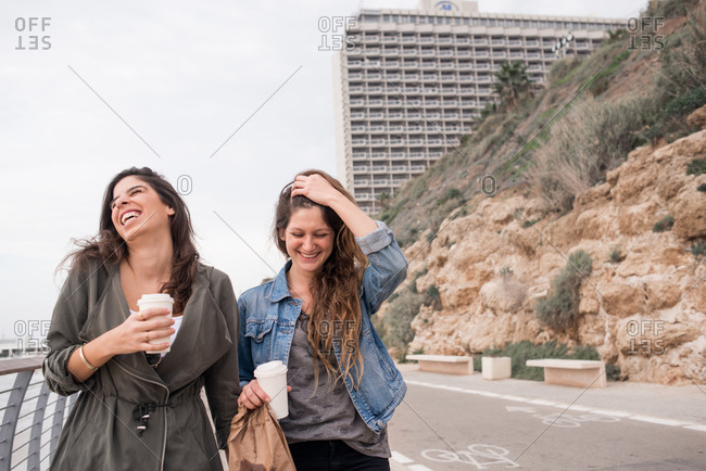 Young women walking outdoors with coffee